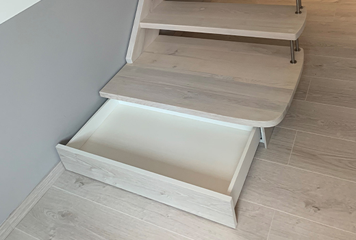 Mit praktischem Stauraum am Fuß der Treppe.